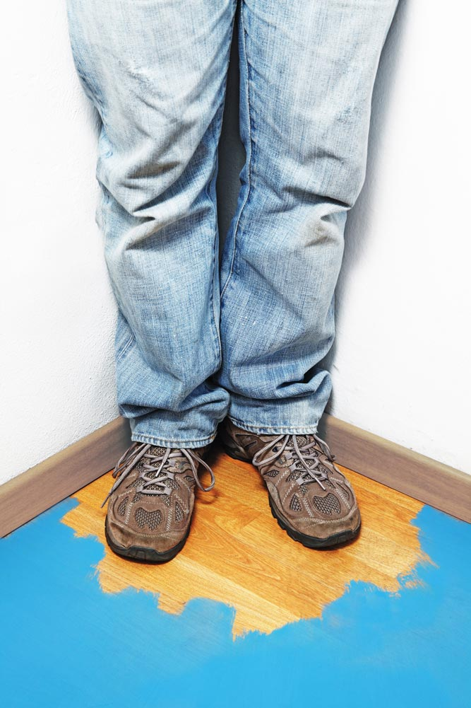 a person trapped into the corner with unpainted wooden floor after painting the rest of the floor with blue paint