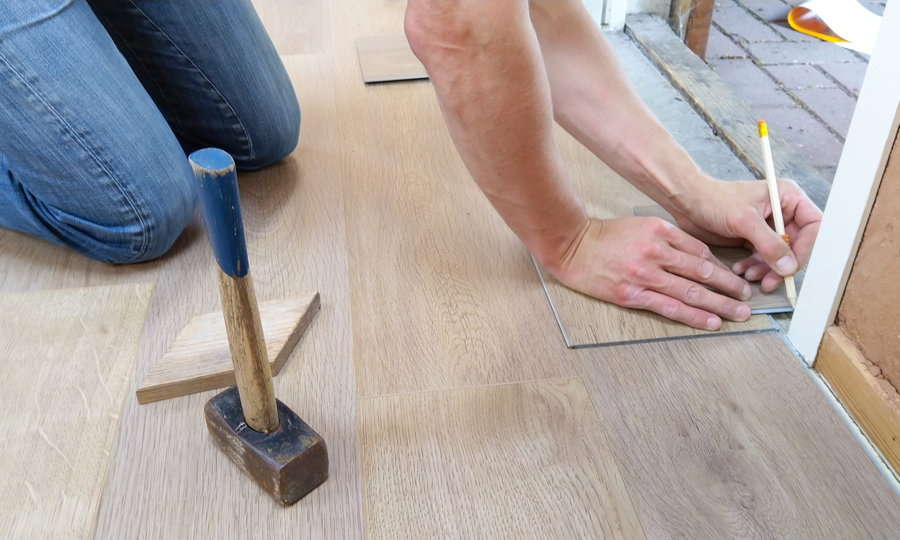 a person taking the measurement on the floor to finish the installation of the laminate flooring near the door area